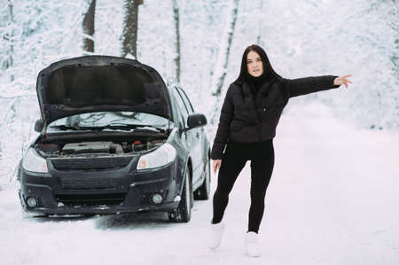 brunette girl waiting for help on the road near a broken car. road assistance Archivio Fotografico