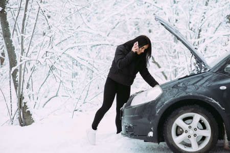 beautiful girl near the motor of a broken car on a winter snowy road. calls for help