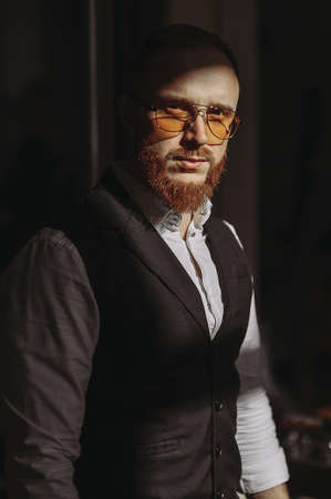 A bearded man with a red beard in a shirt, vest and glasses. success. wealth Archivio Fotografico
