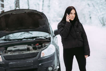 girl calls on the phone near a broken car. waiting for technical assistance