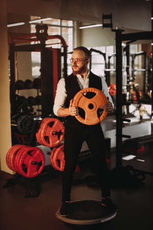 Stylish bearded athlete in a shirt and vest in the gym. holding a dumbbell