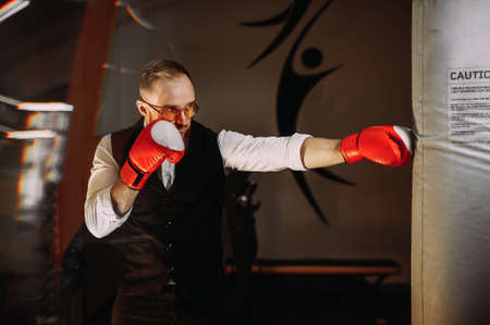 stylish man in a white shirt and black vest is boxing in the gym. red boxing gloves Archivio Fotografico