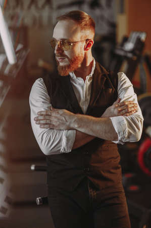 stylish man with a red beard in a white shirt and black vest. success. style Archivio Fotografico