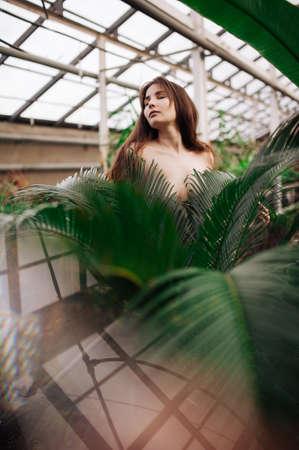 portrait of a beautiful stylish girl in a green batanic garden
