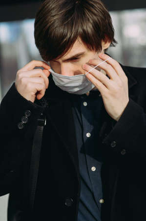 Asian guy in a medical mask in the city. coronavirus. viros protection. Disease epidemic Archivio Fotografico