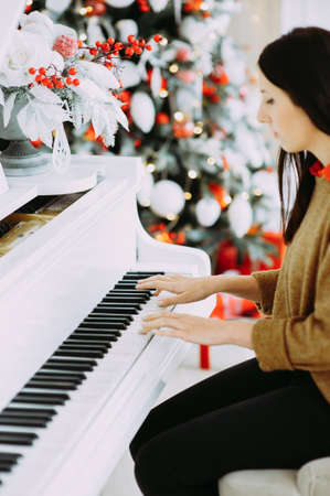 Brunette plays on a white piano against the  Christmas tree.