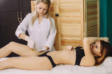 Hair removal at spa luxury studio. Woman legs wax with shugaring. Hot sugar. Archivio Fotografico
