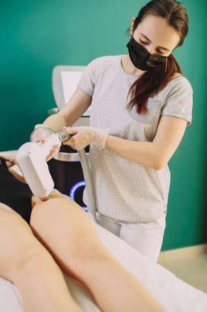 Laser hair removal in professional beauty studio. beauty parlor. Girl master makes hair removal