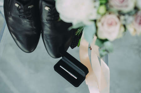 wedding accessories of the groom. the grooms shoes and the brides bouquet on the chair