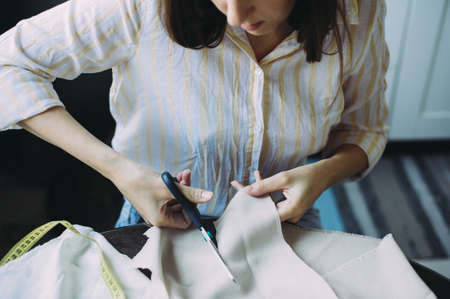 seamstress cuts off with scissors fabric. sewing business. the cloth