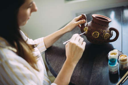 Girl artist paints a clay teapot in her studio. Creativity. Handwork. Art. Self employment