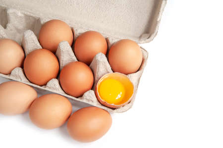 ten chicken eggs in a cage on a white background. isolated. one egg is opened Zdjęcie Seryjne