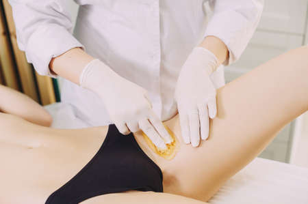 Bikini depilation waxing. The master makes hair removal in the salon
