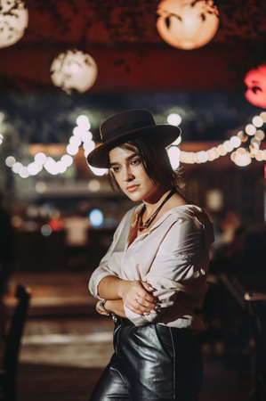 stylish beautiful girl in a hat on a background of lights in a cafe