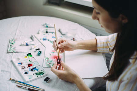 Beautiful girl artist paints with watercolors in a bright studio. Art. Drawing Zdjęcie Seryjne