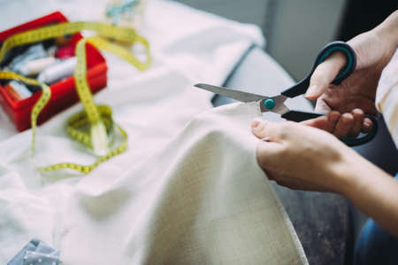 girl master scissors cuts the fabric. handmade. tailor