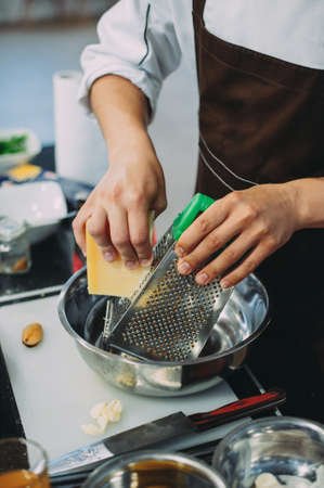 Chef grating cheese, chef hand grating parmesan cheese with grater, Chef rubbing cheese on a grater, close up Archivio Fotografico - 145350503