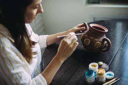 Girl artist paints a clay teapot in her workshop. Creativity. Handwork. Art. Self employment