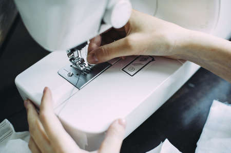 the master works on a sewing machine. thread the needle. seamstress. production. clothes. the cloth Stockfoto