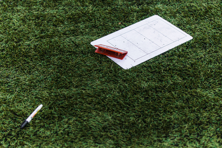 Coachs board and pen on the grass background