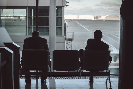Rear view of two businessmen as they stare out a large window with a airport view. 写真素材