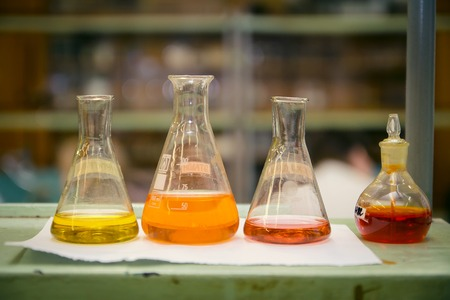 In lap at school,university,science chemistry concept. Laboratory test tubes and flasks with color liquid put on white table for work,check and test chemistry.