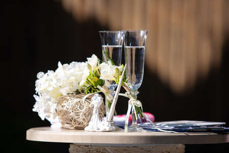 On the table are white flowers in a beige wicker flowerpot, a fountain pen, a small statuette and wine glasses Reklamní fotografie