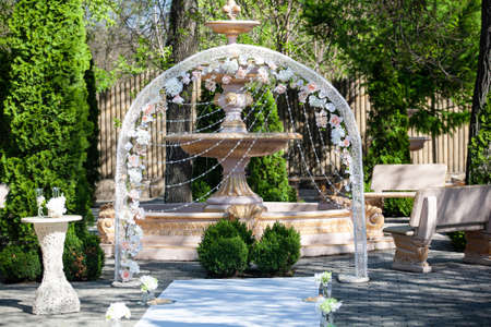 Arch decorated with white soft blue and beige flowers against the background of a fountain, boxwood bushes and other greenery