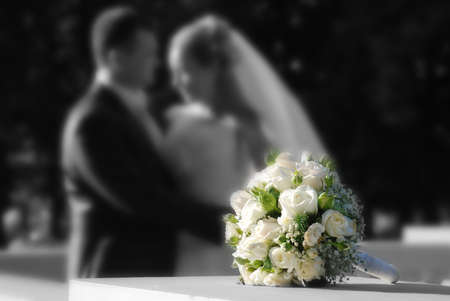 Bunch of white roses and newly-weds on a blackly white background Stock Photo