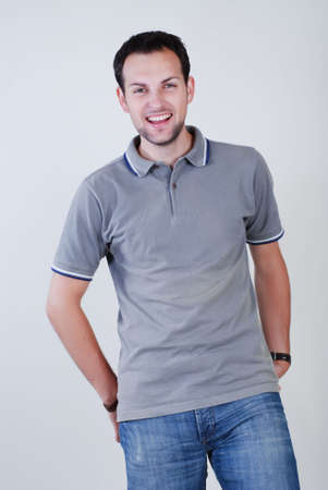 young fellow: Portrait of young fellow dressed in a grey sport shirt and dark blue jeans Stock Photo
