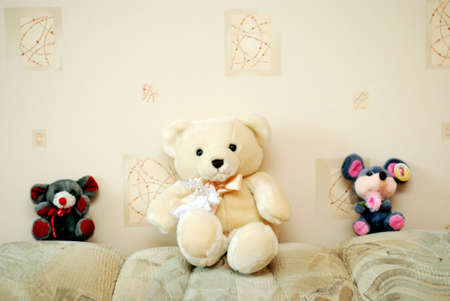 Three toy animals: one white bear and two mice are sitting next to a wall photo