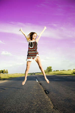 Jumping happy girl over the road under blue sky photo