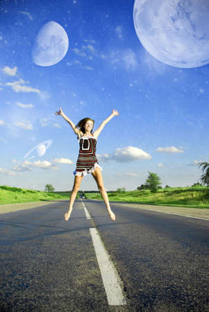 Happy woman jumping over the road under blue sky with planets photo
