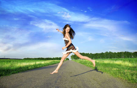 Happy woman jumping over the road under blue sky