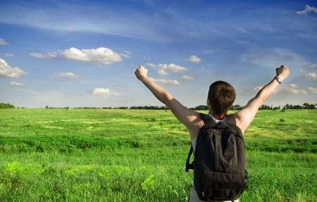 Man winner traveler on the meadow with green grass and blue sky Stock Photo