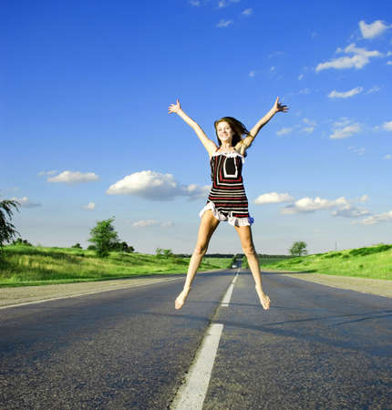 Jumping happy woman under blue sky on the road photo
