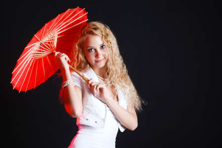 Portrait of young beauty woman in white dress at black background with umbrella photo