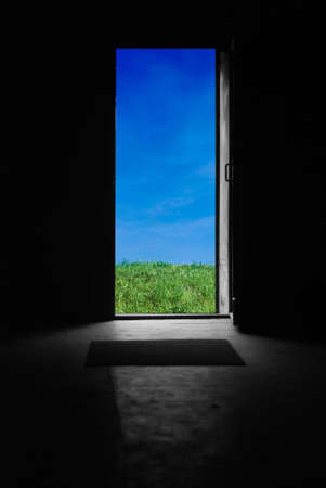 Opened door with green grass and blue sky over it photo