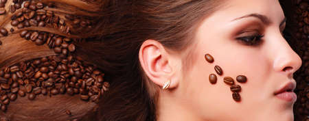 coffee beans on the hair and face of beautiful young woman photo