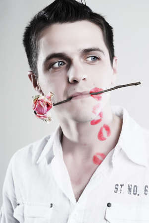 Red kisses on face of young man with rose at white background photo