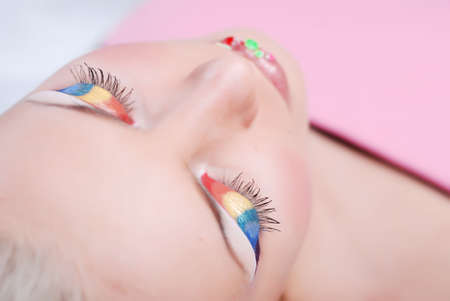 Face of beautiful girl with make-up as a rainbow on eyes and lips photo