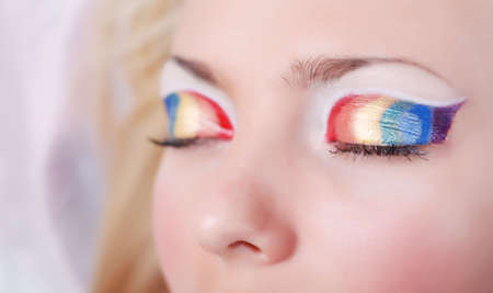 Face of beautiful girl with make-up as a rainbow on eyes photo