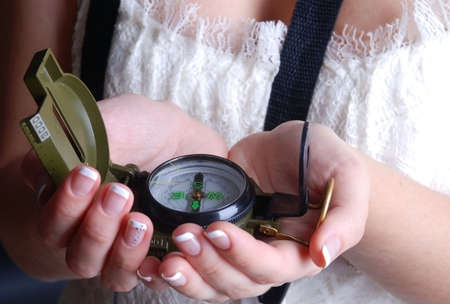 Woman takes a compass in hands photo