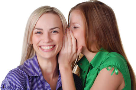 two beautiful happy young friends are whispering Stock Photo