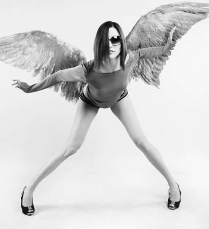 Girl with wings after the back, tries to keep equilibrium photo