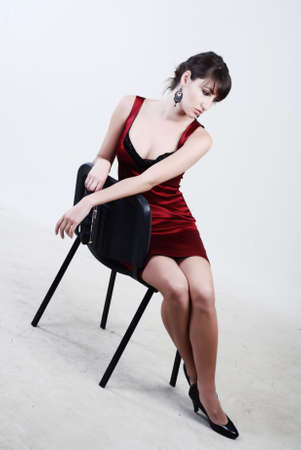 designer chair: A beautiful young girl is dressed in red clothes sits nea chair and looks aside Stock Photo