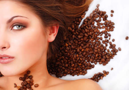 portrait of beautiful young woman with coffee beans around her face Stock Photo