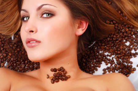 portrait of beautiful young woman with coffee beans around her face photo