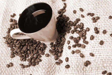 cup of coffee with coffee beans on the hessian  photo