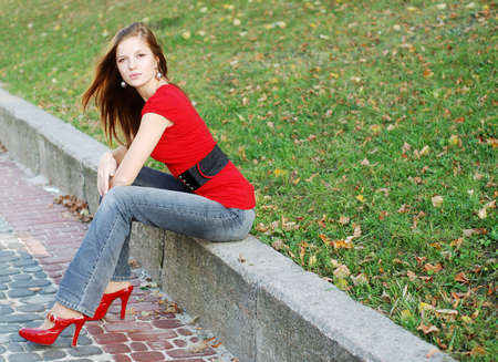 beautiful woman sit on a road kerb in park photo